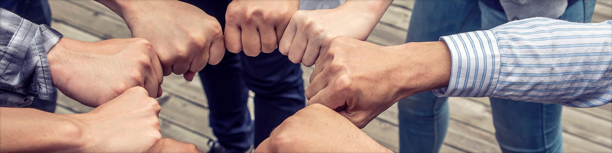 People Putting Their Hands Together In Cooperation